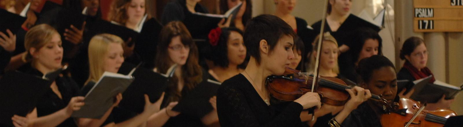 loyola student playing the violin while the choir is singing in the background