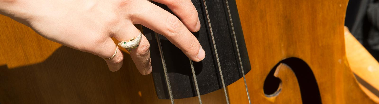 A close up of a student playing the bass (strings)