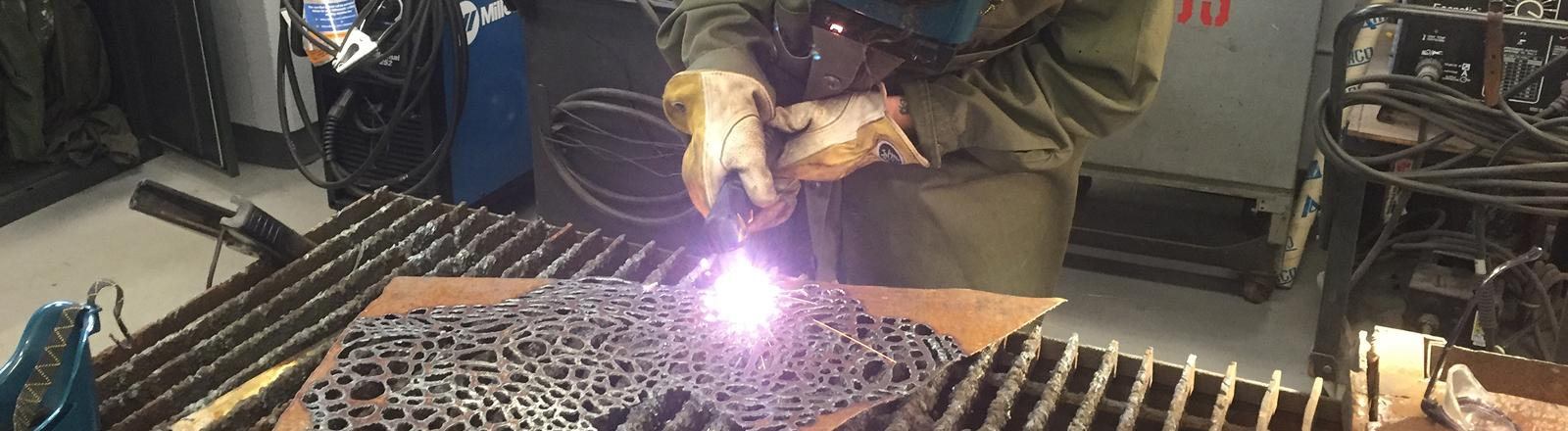 A Loyola Art student uses a blowtorch to make a sculpture.