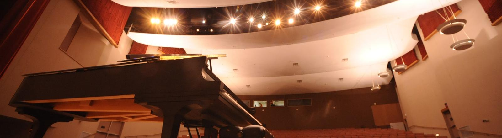 A piano on stage with roussel hall in the background