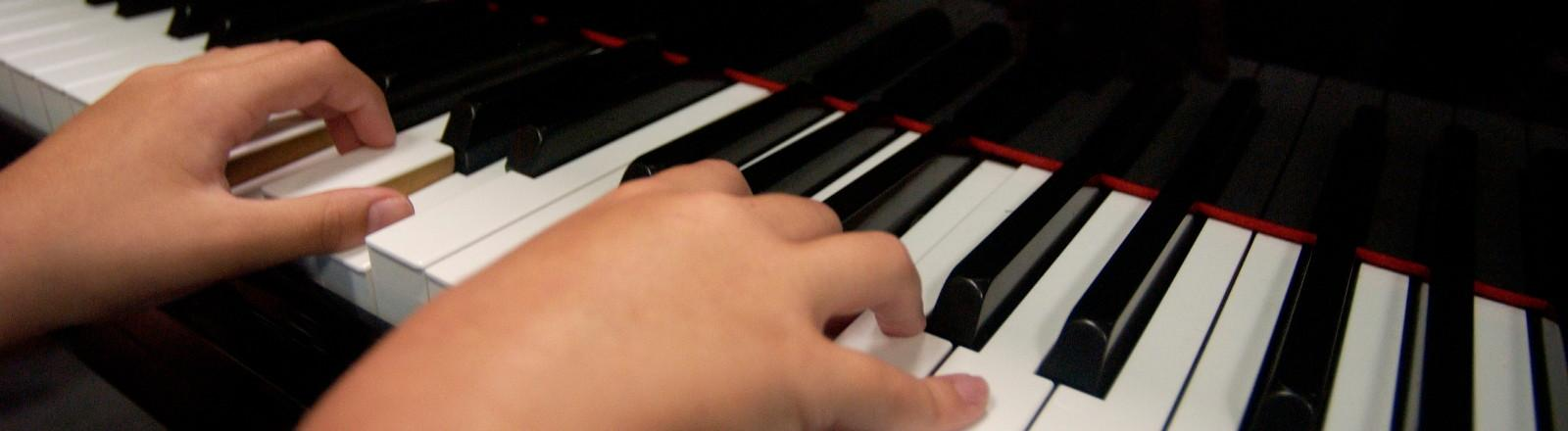 The hands of a child playing the paino
