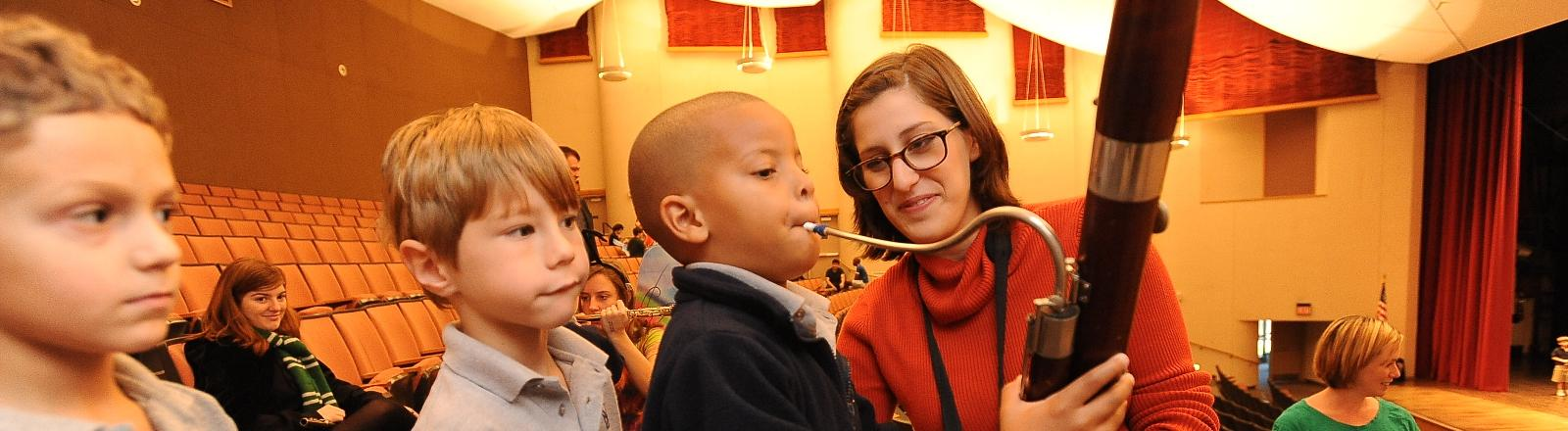 A Loyola School of Music music education student helps an elementary student play a bassoon.