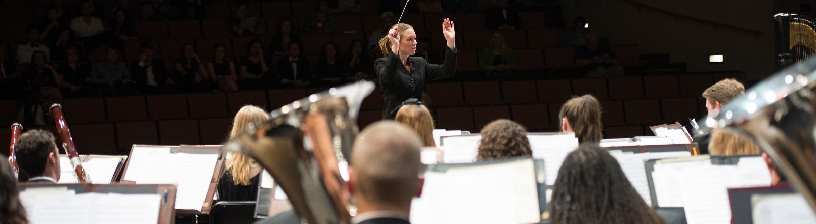Dr. Serena Weren conducts the Loyola Wind Ensemble in Roussel Hall.
